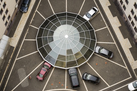 courtyard: Web-shaped car parking around glass dome in the courtyard Stock Photo