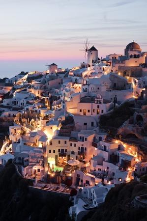 fira: Oia village at sunset with illumination turned on, Santorini, Greece