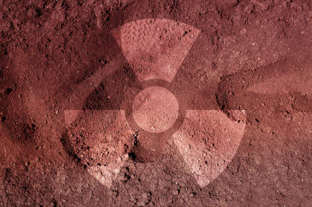 irradiation: A radiation warning symbol on soil with tracks. An ecological concept. Stock Photo