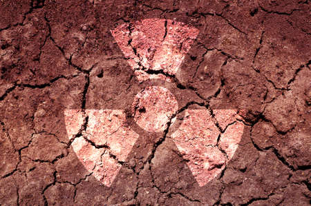 hazardous material: A radiation warning symbol on cracked soil. An ecological concept.