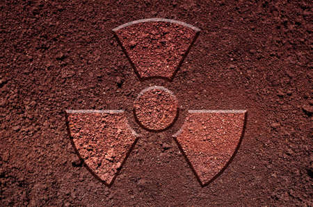 fallout: A radiation warning symbol, made of soil. An ecological concept.