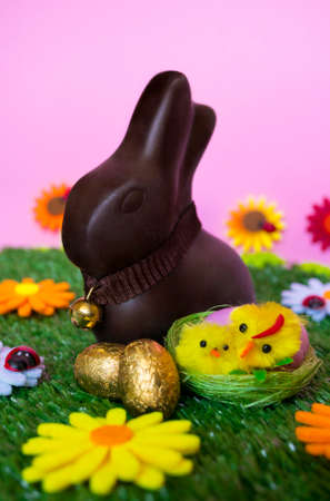 An Easter background with an Easter chocolate bunny, some easter eggs, flowers, grass. Stock Photo