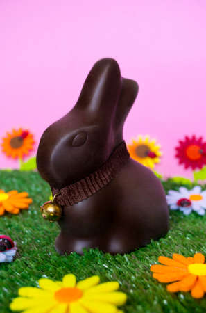 easter flowers: An Easter background with an Easter chocolate bunny, flowers, grass.