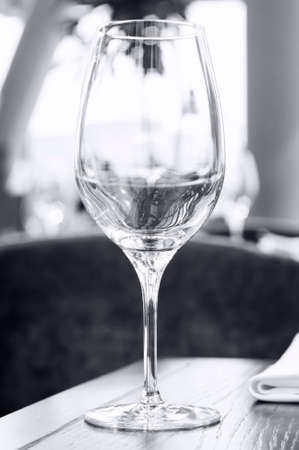 An empty single wine glass on a wooden table in a restaurant.