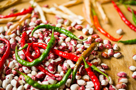 old styled: Lots of chili peppers and beans on the wooden surface. Selective focus. Stock Photo
