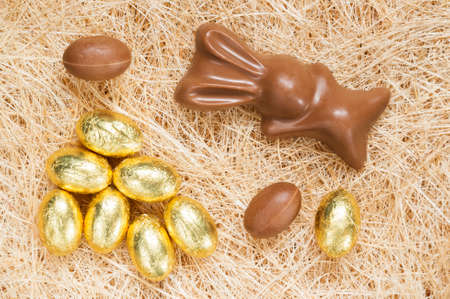 A chocolate Easter bunny with some chocolate eggs on a straw background.