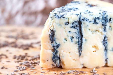 stilton: A piece of an amazing fresh blue cheese on a wood board.