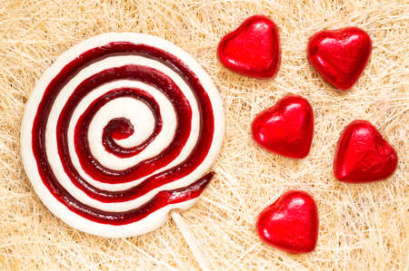 sugarplum: A retro looking photo of lollipop and heart shaped candies on a straw background. Stock Photo