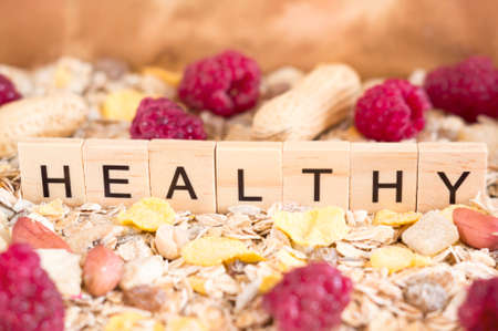 The word Healthy is standing on the lots of corn and oatmeal flakes. Healthy lifestyle concept.
