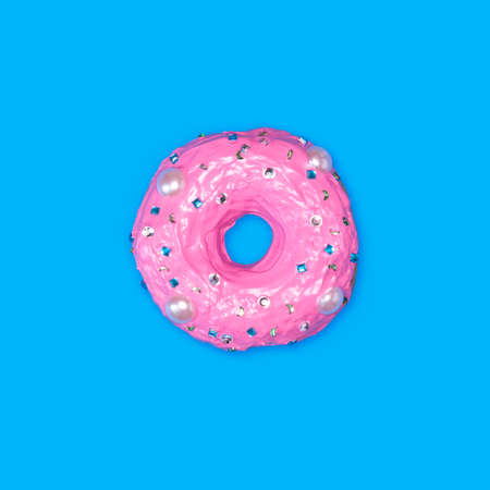 A photo of a donut, decorated with caramel, which looks like rhinestones, on blue background.