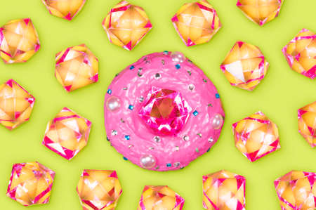 A photo of a donut with a plastic rhinestone on the top of it and lots of rhinestones around it.