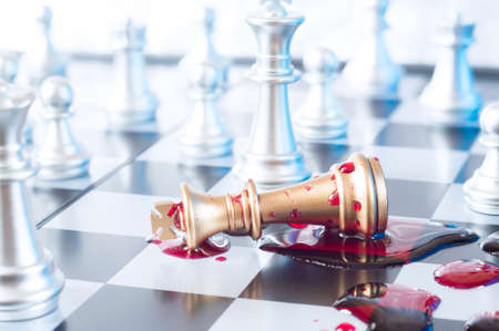 A conceptual photo with chess pieces and blood on a chessboard. Business, law or political concept, which could represent the war of corporations, geopolitical situation and so on. Selective focus. 스톡 콘텐츠