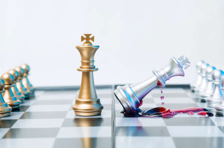 A conceptual photo with chess pieces and blood on a chessboard. Business, law or political concept, which could represent the war of corporations, geopolitical situation and so on. Selective focus. Stock Photo