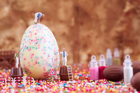 Toy painters are decorating an Easter egg. Toy concept for Easter.