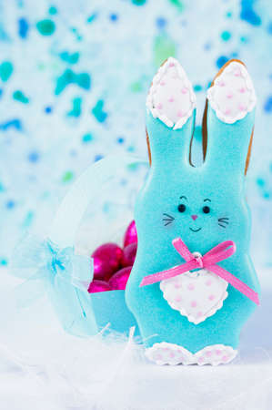 A background with a handmade honey-cake rabbit and a paper basket full of Easter eggs for an Easter party or other events.