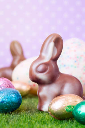 Easter bunnies, made of white and milk chocolate against a polka dot background.