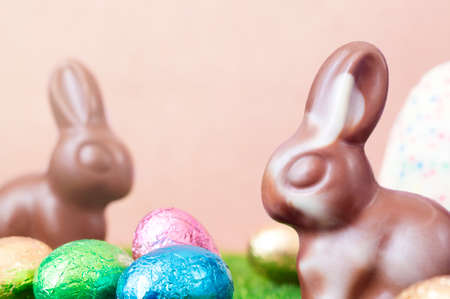 Easter bunnies, made of white and milk chocolate against a carton background. Imagens