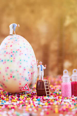 Toy painters are decorating an Easter egg. Toy concept for Easter. Soft light.