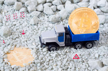 A photo of bitcoins, a toy truck and a road sign. Bitcoin mining, blockchain concept.