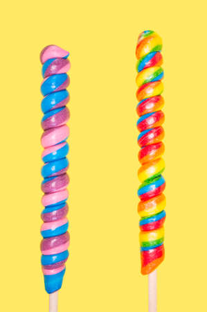 Two long colorful lollipops on a yellow background.
