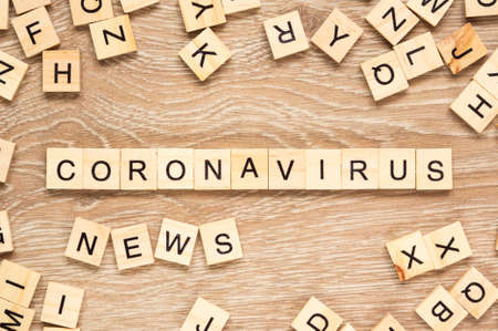 """The words """"Coronavirus News"""" spelt out with letter tiles on the wooden background Archivio Fotografico"""