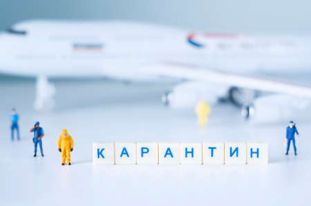 Group of toy people isolate a plane and its passengers. The Russian word means `Quarantine`.