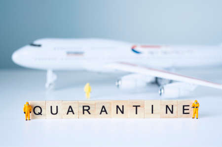 Group of toy people isolate a plane and its passengers. Quarantine concept. Stock Photo