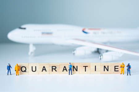 Group of toy people isolate a plane and its passengers. Quarantine concept. 写真素材