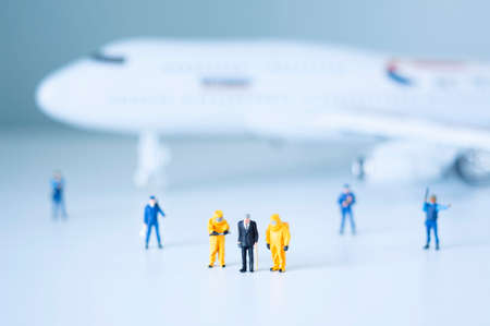 Group of toy policemen and scientists isolate a plane and its passengers. Quarantine or toxic person isolation concept.