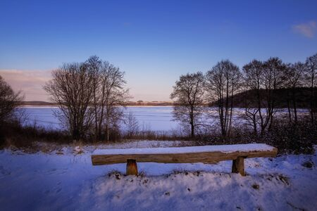 An empty bench in front of the Breite Luzin in the Feldberg lake district