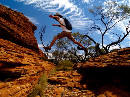 Australian Kings Canyon with typical red rocks and blue sky, Person jumping over crevice photo