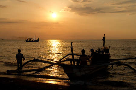 Fishermen at beach during sunset photo