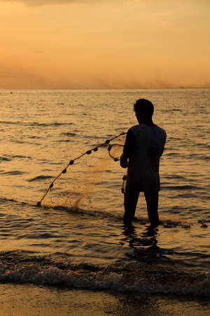 Fisherman at beach with fishing net during sunset photo