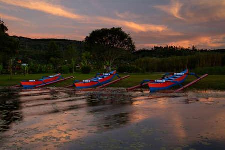 Boats at lake in sunrise photo