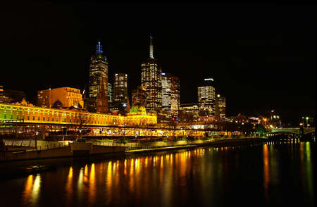flinders: Melbourne Skyline of City Centre at night, reflections in Yarra River, Bridge, Federation Square, Flinders Station    Stock Photo