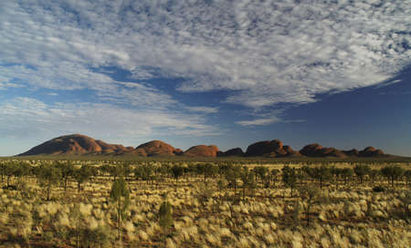 Kata Tjuta in sun, red, with blue cloudy sky     photo