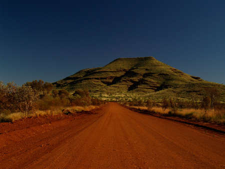 Australia Dirt Road with red Sand in front of green Hill photo