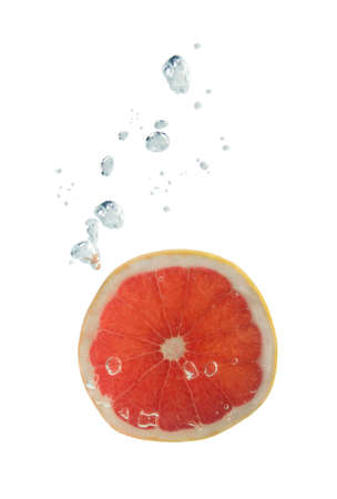 comestible: Grapefruit falling into water, with air bubbles, in front of white background, union of the three things essential to live which is air, water and nutrition