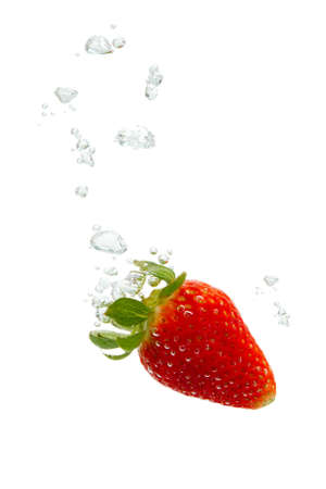 Strawberry falling into water, with air bubbles, in front of white background, union of the three things essential to live which is air, water and nutrition photo