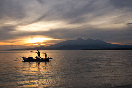 lombok: Sunrise above volcano Rinjani with fishing boat, Lombok Stock Photo