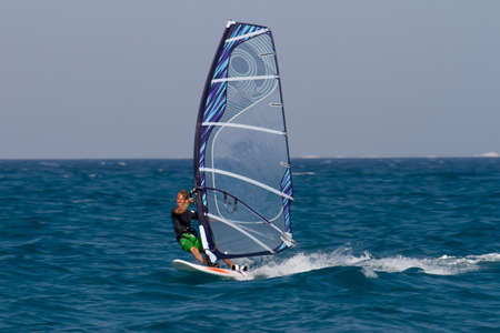 hurghada: Windsurfing in Egypt, Hurghada. Man surfing with blue sail on ocean. Stock Photo