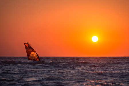 windsurf: Windsurf durante la puesta de sol en el mar Foto de archivo