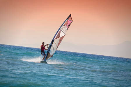 sail board: Windsurfing in Rhodes Greece. Man surfing on blue with oceanwith red sky, Iceland in the background.