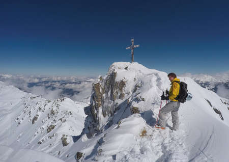 yellow jacket: Man with yellow jacket climbing a mountain with snow in winter in Austria Stock Photo