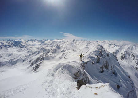 snow climbing: Man with yellow jacket climbing a mountain on a ridge with snow in winter in Austria Stock Photo