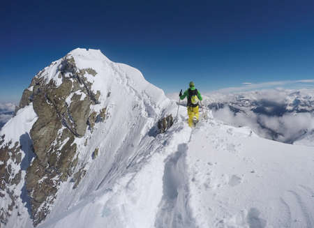 snow climbing: Man with yellow trousers and green jacket climbing a mountain with snow in winter in Austria