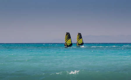 windsurfers: Two windsurfers ride parallel to sea, with similar sails.