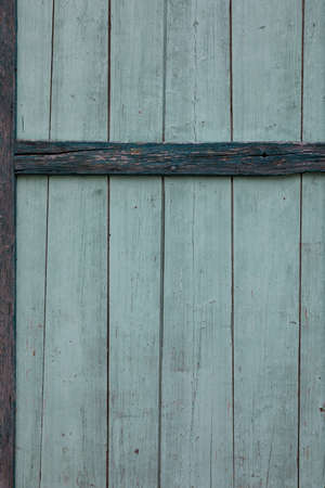 Old wooden barn door in green turquoise painting, already coming off Stock Photo