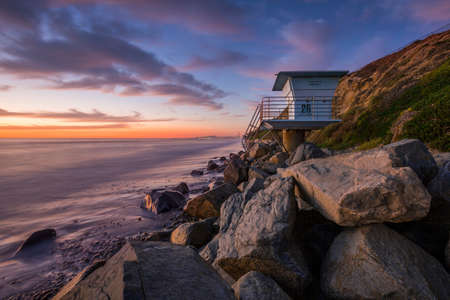 Sunset at beach at West Coast in California with lifeguard tower, clods and colors in the sky, USA