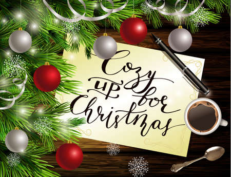 cozy: Christmas New Year design dark wooden background with christmas tree and silver and red balls and handwritten Cozy up for Christmas coffee teaspoon and pen